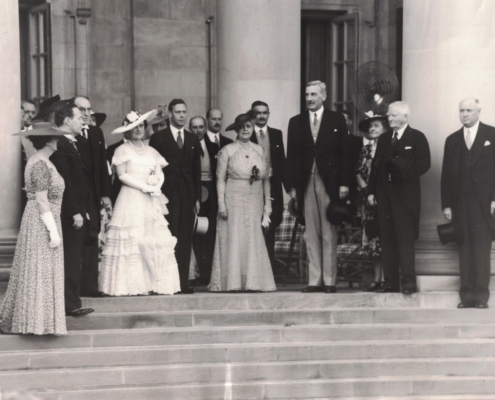 United Kingdom king george VI and his wife queen elizabeth standing at top of stone steps with dignitaries