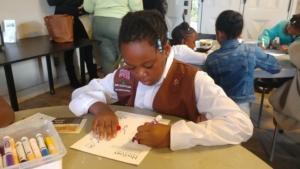 girl coloring in workbook facing forward
